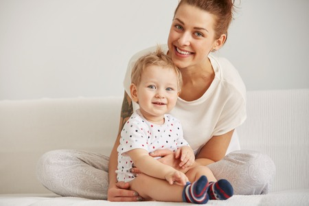 lazy: Young mother with her one years old little son dressed in pajamas are relaxing and playing in the bedroom at the weekend together, lazy morning, warm and cozy scene. Selective focus.