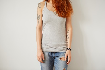 blank template: Girl wearing grey blank t-shirt standing on the background of a white wall.