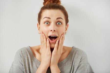 asombro: Sorpresa de la mujer sorprendida. mujer Retrato de detalle que parece sorprendida en su totalidad incredulidad amplia boca abierta aislados fondo gris de la pared. emoción humana lenguaje corporal expresión facial positiva. Chica divertida Foto de archivo