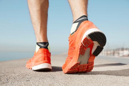 hacer footing: pies de atleta corredor ejecutan en primer plano de carreteras en el zapato. la aptitud del hombre ejercicios de desplazamiento concepto de bienestar. las piernas de corredor del hombre y zapatos en la acción en la carretera al aire libre en la carretera cerca del mar.