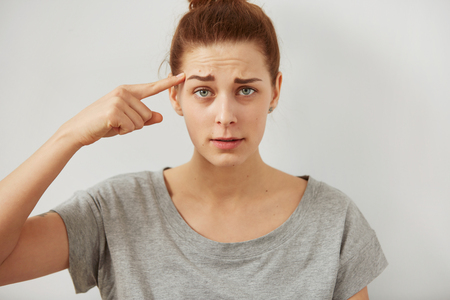 bawl: Closeup portrait indignant young freelancer woman looking at camera holding  finger at head with disgusting emotion on her face isolated grey wall background. Human emotion, reaction, expression.
