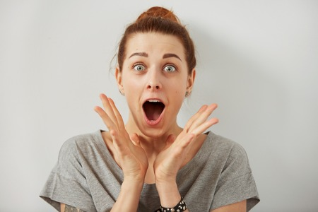 Surprise astonished woman. Closeup portrait woman looking surprised in full disbelief  wide open mouth isolated grey wall background. Positive human emotion facial expression body language. Funny girl Stok Fotoğraf