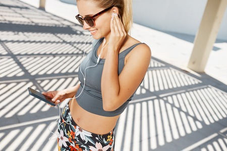 listening music: Sport, training, technology, fitness and lifestyle concept. Fitness woman in sportswear listening music with headphones after training outdoors at beautiful sunny day. Stock Photo