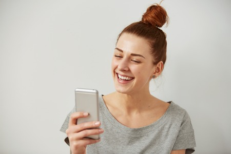 lachendes gesicht: Nahaufnahmeportrait lächelnd oder junge Freiberufler Frau am Telefon lachen suchen gute Nachrichten oder Fotos mit schönen Gefühl zu sehen, auf ihrem Gesicht isoliert Wand Hintergrund. Menschliche Emotionen, Reaktion, Ausdruck.
