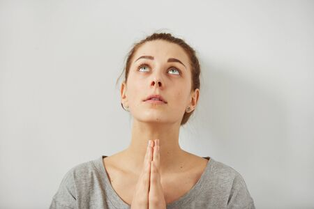 body language: Closeup portrait of a peaceful woman praying. Sad woman prays holding clasp hands together, concept of girl problem, stress, depression. Human emotion facial expression body language.