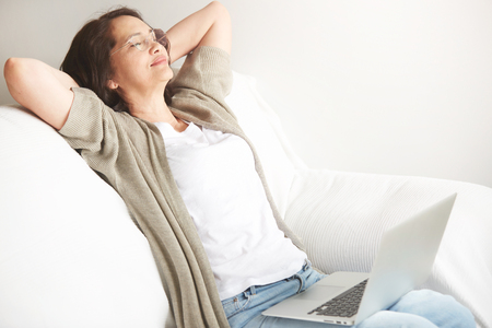 silver surfer: Portrait of attractive middle-aged brunette businesswoman in eyeglasses at home working on laptop computer while work at office work. Content woman sitting on her couch using laptop smiling in room Stock Photo