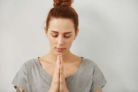 christian women: Closeup portrait of a peaceful woman praying. Sad woman prays holding clasp hands together, concept of girl problem, stress, depression. Human emotion facial expression body language.