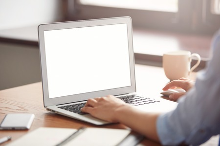Cropped view of a young office worker sitting at the table in caf? enjoying her coffee after hard day at work. Female hands keyboarding on the laptop with copy space for your text message or promotional content Stockfoto