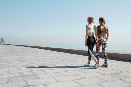 Young female runners enjoying rest after physical training while walking against blue sky backgroundwith copy space area for your text message or content. Athletic women having break after workout Stock Photo