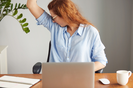 intolerable: Portrait of a young woman wearing blue shirt disgusting with bad smell of her wet armpit while working in the office. Something stinks, negative human emotions, facial expressions, feeling reaction Stock Photo