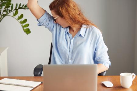 Portret van een jonge vrouw, gekleed in blauw shirt walgelijk met slechte geur van haar natte oksel tijdens het werken in het kantoor. Iets stinkt, negatieve menselijke emoties, gelaatsuitdrukkingen, het gevoel reactie
