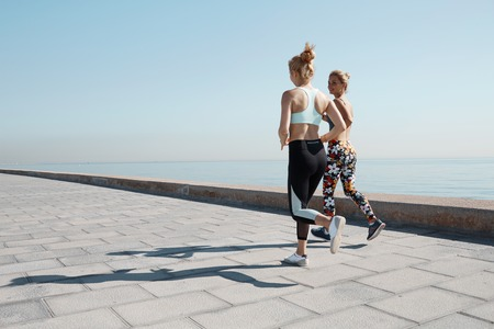 Two young female runners exercising outdoors training together for marathon. Caucasian running partners working out outdoors on sunny day. Two fit female joggers talking and smiling during workout on the beach.