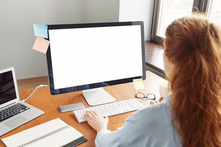 Blank white computer screen with girls hands and office accessories on wooden table, mock up. Cropped view of young redhead female manager working in her office, typing text on keyboard