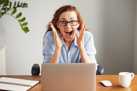 Portrait eines Redheadmädchens nett Brille und blauen Hemd trägt mit Aufregung und Freude zu schreien, während auf ihrem Laptop arbeiten. Kopfbild eines aufgeregten weiblichen Studenten mit dem Gewinn Ausdruck auf ihrem Gesicht