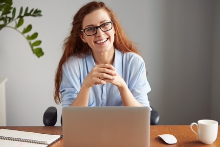 Cheerful young businesswoman in casual shirt and glasses looking and smiling at the camera. Happy successful female entrepreneur enjoying productive day while sitting in front of the computer Stockfoto