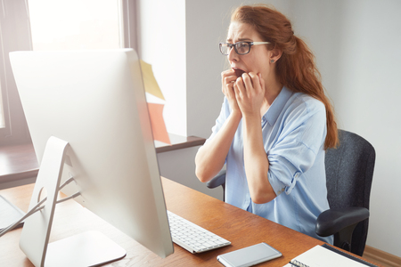 Stressed shocked businesswoman sitting at the table in front of computer in the office looking stunned, mouth wide open. Negative human face expressions, emotions, body language reaction