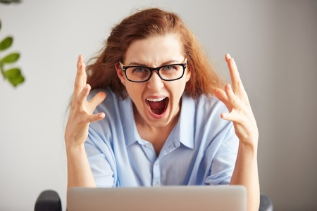 Portrait of a young attractive businesswoman with frustrated look working on laptop at the  office. Outraged screaming freelance student looking at the camera with desperate expression: I hate this computer Stock Photo