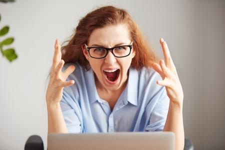 Retrato de una joven empresaria atractiva con mirada frustrada que trabaja en la computadora portátil en la oficina. Indignados gritando estudiante independiente mirando a la cámara con expresión desesperada: No me gusta este equipo