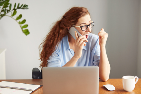 excitement: Headshot of a successful businesswoman looking excited talking on the cell phone. Portrait of a female freelancer shouting with excitement and joy. Attractive female manager winning business sitting in her office Stock Photo