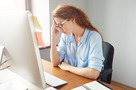 Concerned female entrepreneur looking at the computer screen while working in the office. Stressed young woman sitting at the desk and leaning on her elbow while thinking on something important