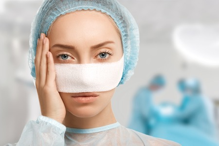 Headshot van jonge vrouwelijke gezicht met pleister. Sluit omhoog portret van vermoeide vrouwenpatiënt, wat betreft haar gezicht na plastische chirurgie, uitgeput bekijkend de camera met artsen die op de achtergrond werken