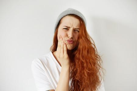 Headshot van roodharige tiener vrouw op haar wang met pijnlijke uitdrukking alsof ze die vreselijke kiespijn. Negatieve menselijke emoties, gezichtsuitdrukkingen, lichaamstaal. selectieve aandacht