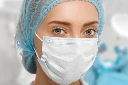 cirujano: Headshot de la mujer joven cirujano en la gorra azul y una m�scara quir�rgica blanco mirando a la c�mara con colegas que realizan en el fondo de la sala de operaciones. Concepto m�dico y la cirug�a pl�stica