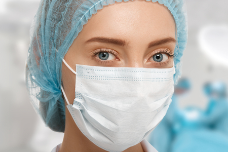 surgeon mask: Headshot of young female surgeon in blue cap and white surgical mask looking at the camera with colleagues performing in the background of the operation room. Medical and plastic surgery concept