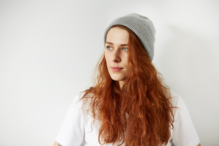 Close up studio portrait of attractive young female looking away with dreamy and mysterious smile. Headshot of pretty girl with loose red hair in cap and white T-shirt. Film effect, selective focus