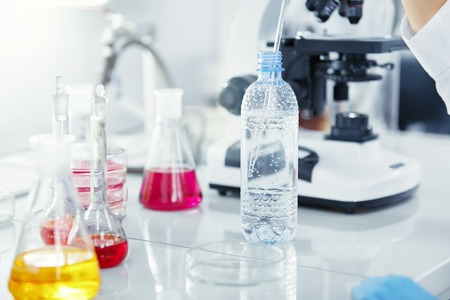 Close up view of female medical researcher or doctor using glass pipe and plastic bottle while working in chemical laboratory (biochemistry, genetics, forensics, microbiology). Selective focus Reklamní fotografie