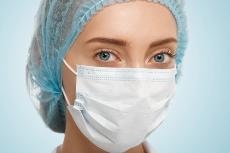 facemask: Close up view of cute Caucasian blue-eyed woman doctor wearing blue cap and white facemask looking at the camera isolated against studio background. Healthcare, medical and plastic surgery concept Stock Photo