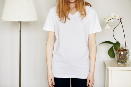 skinny jeans: Beautiful Caucasian teenage girl, cropped portrait. Young attractive woman with loose red hair wearing blank white T-shirt and black skinny jeans while standing against home interior background