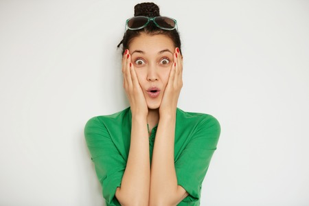 sensational: Cropped isolated portrait of beautiful astonished woman looking at the camera, surprised with big sale prices. Headshot of brunette female holding her face in shock after receiving some sensational news