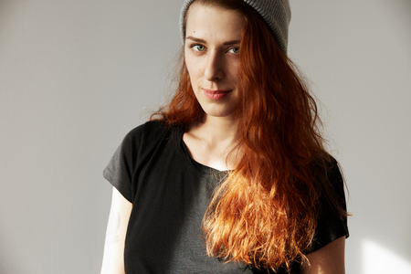 finishing school: Picture of young woman looking at the camera with concentrated expression. Student girl with long red hair in T-shirt making plans for future after finishing school, with serious and confident look