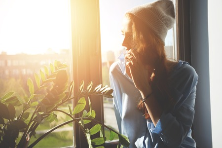 appointing: Cropped portrait of female designer discussing new collection on cell phone while sitting at the window. Woman freelancer enjoying sunshine talking on mobile phone and appointing meeting with clients