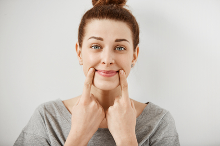 Headshot of young Caucasian woman making fake smile with her fingers stretching the corners of her mouth. Portrait of student girl trying to stay positive after failing final exams at university