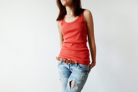 sleeveless top: Attractive young brunette female with slim and fit body posing isolated against white studion wall wearing red sleeveless top and ripped jeans. Student girl dressing up before going to university Stock Photo