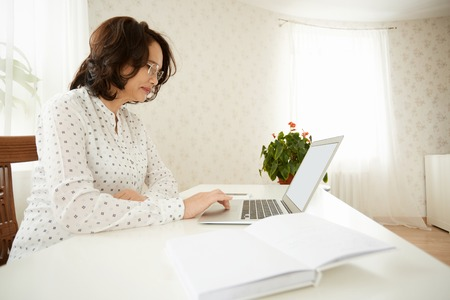 silver surfer: Side view of serious mature woman in glasses using wireless Internet connection on laptop, shopping online or reading news, sitting at the white table against home interior background. Selective focus