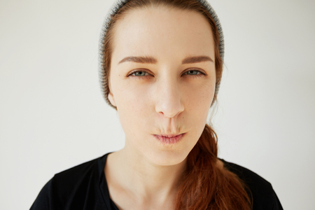 business skeptical: Close up portrait of skeptical young woman looking suspicious, with disgusted expression on her face, mixed with disapproval, isolated against white background. Negative human emotions, and feelings