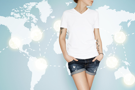 advertising design: Advertising and T-shirt design concept. Cropped portrait of young female posing in white copy space T-shirt for your promotional content against world map interface background. Digital visual effects Stock Photo