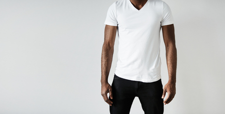 T-shirt design and advertising concept. Cropped portrait of black male with athlete body wearing black skinny jeans and white blank T-shirt with copy space for your text or promotional content. Standard-Bild