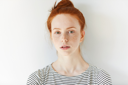 Close up of female teenager with healthy clean fresh skin with freckles wearing sailor shirt, looking at the camera. Portrait of student girl with red hair and blue eyes. Youth and skin care concept Foto de archivo