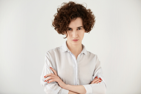 Portrait of young vexed brunette woman standing with arms folded against white concrete wall background. Serious female entrepreneur with curly short hair displeased with working process in the office