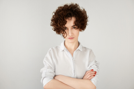 disapproving: Headshot of serious young woman with disapproving expression on her face posing isolated against white copy space wall for your text or promotional content. Confident female boss suspecting someone