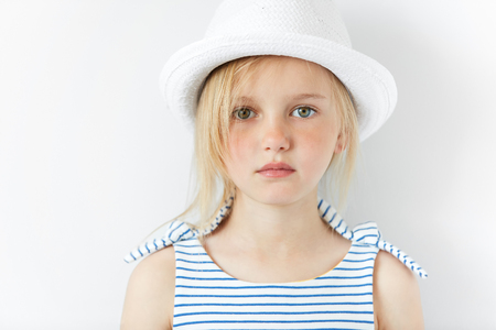 youngsters: Cute preschool girl with green eyes and blonde hair wearing striped dress and white hat looking at the camera while posing against white studio wall background. Pretty serious little female model