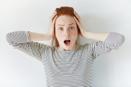 Headshot of hysterical Caucasian freckled student girl with ginger hair looking in despair and panic, being late for important exam or event, not knowing what to do, hands on her head, mouth wide open
