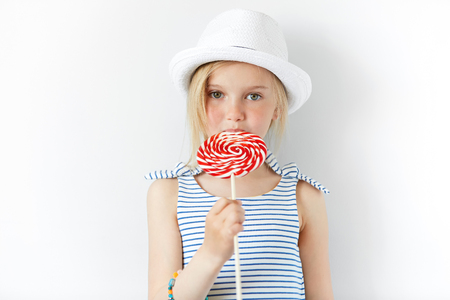 provocative food: Lifestyle and people concept. Adorable little female child with green eyes and fair hair in white hat and striped dress, posing with candy in her hands, spending weekend with her grandparents Stock Photo