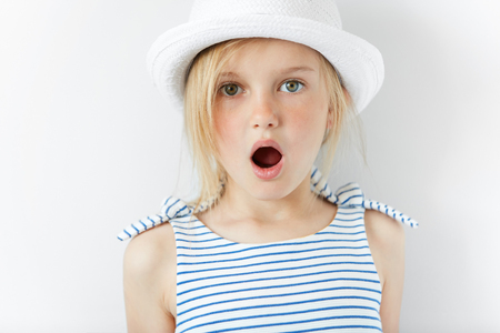Close up portrait of amazed adorable little girl in white hat and striped dress, having fun indoor, looking at the camera in excitement, astonished with something. Human face expressions and emotions