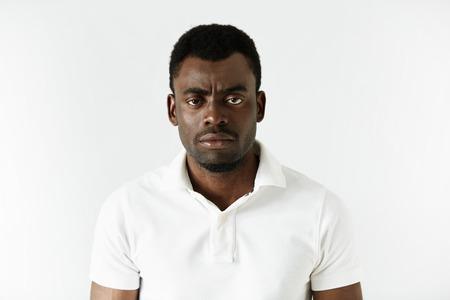 불쾌 한 식 카메라를 찾고 흰색 폴로 셔츠에 화가 또는 짜증이 젊은 아프리카 계 미국인 남자의 초상화. 부정적인 인간의 표현, 감정, 감정. 신체 언어
