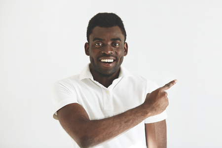Look at that! Headshot of handsome young African man in white polo shirt looking and smiling at the camera with cheerful expression on his face, pointing a finger at the copy space for your content